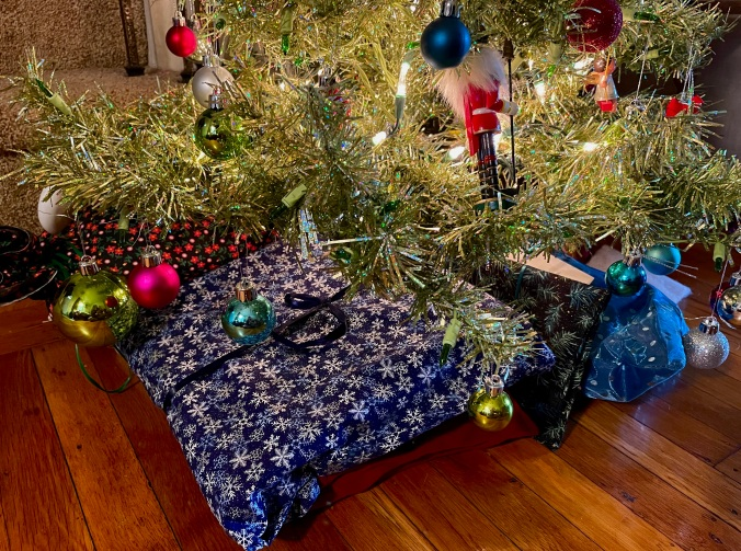 gifts in reusable cloth bags under a Christmas tree