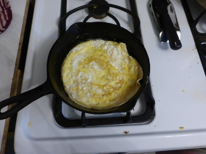 flat circle of cooked egg in pan with tortilla sticking up at the edge