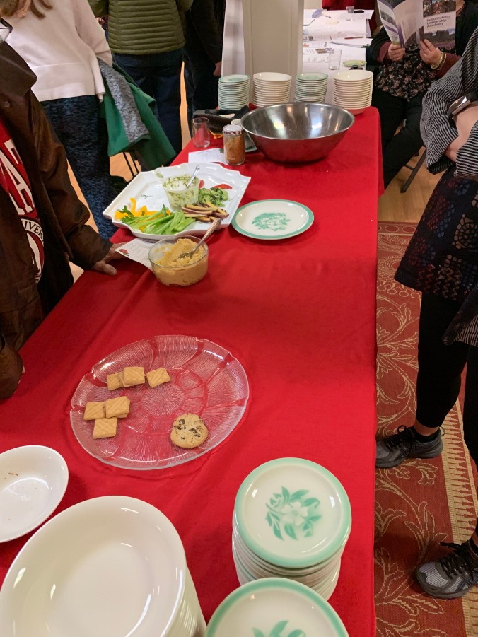 buffet with mostly-empty plates of vegetables and cookies and popcorn
