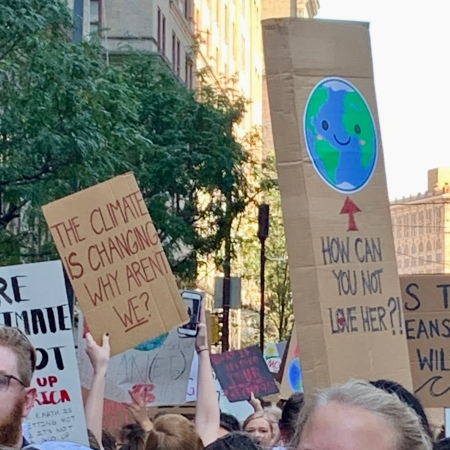 "protest signs: ""The climate is changing; why aren't WE?"" and smiling Earth captioned, ""How can you not love her?!"""