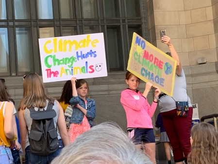 "Children holding signs: ""Climate change hurts the animals"" and ""No more climate change"""