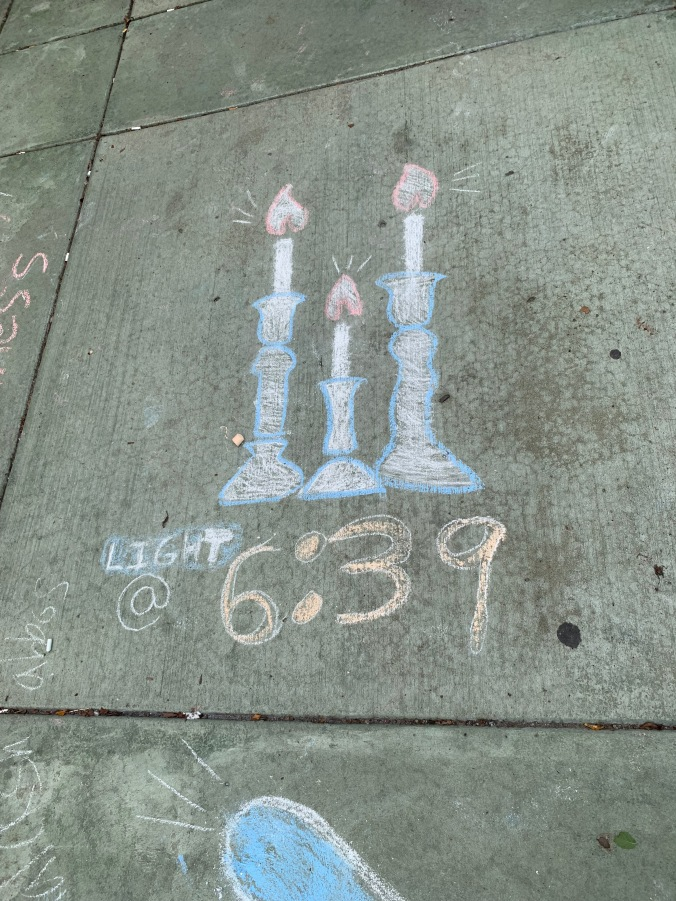 "sidewalk chalk drawing of candles and ""6:39"""