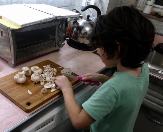 Five-year-old slicing mushrooms with paring knife