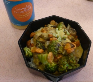 jar of Simply Balanced Panang Ginger Curry Sauce alongside bowl of vegetables, lentils, and rice topped with the sauce
