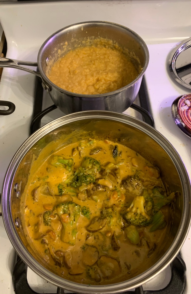 two pots on stove: vegetables in yellow curry sauce in front, red lentils in back