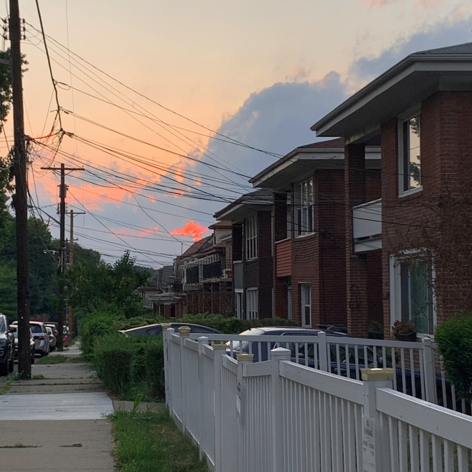 sunset seen through power lines above a row of brick duplexes and sidewalk