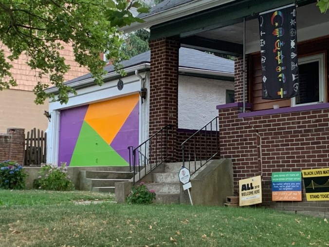 boring white garage with door painted in op-art blocks of purple, orange, and lime green; next to house with religious-inclusivity banner, several social-justice signs, and security-system sign