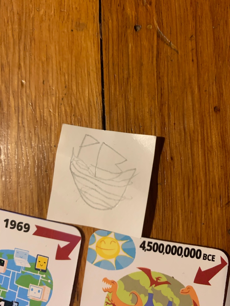 A small square of paper with a child's drawing of a ship, placed next to Time Breaker tiles.