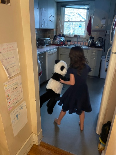 a little girl dancing with a large stuffed panda, in her kitchen; snowy branches visible out the window