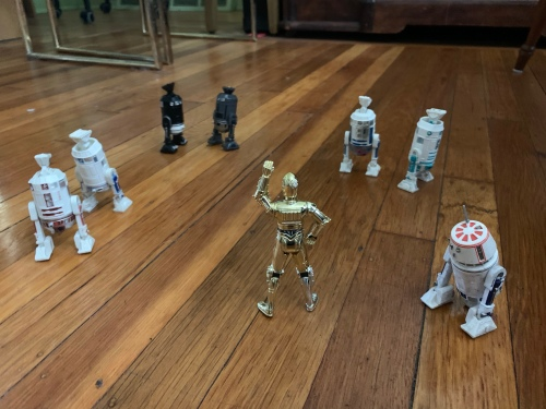 Star Wars action figures on a hardwood floor. C3-P0 has an authoritative stance with upraised arm. Six assorted R2 units are standing on their side legs with torso upside down and central foot in the air. R5-D4 is turned away toward the right.
