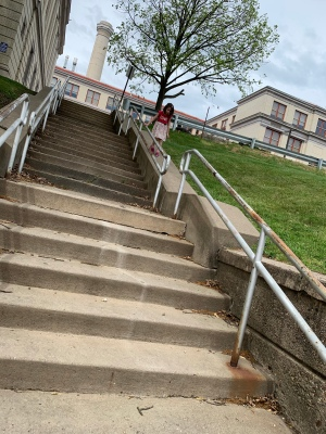 a little girl walking down the slanting concrete wall at the side of a tall staircase, holding onto the banister from the outside; a tree is just leafing out for spring