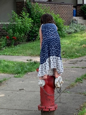 child in an ankle-length batik sundress standing on a fire hydrant on a sidewalk in front of small lawns