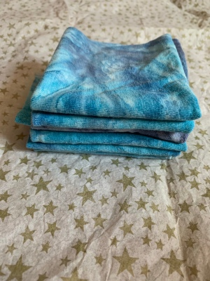 folded squares of blue tie-dye fabric atop tissue paper printed with gold stars