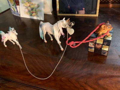 two toy unicorns connected by a necklace chain over their horns, with heart-shaped pendant dangling in front of the larger unicorn's face; a small bungee cord is hooked to the necklace and looped around the shoulders of a toy lion cub standing on top of a Rubik's cube; the whole scene is positioned in front of greeting cards and a portrait displayed on top of a wooden chest