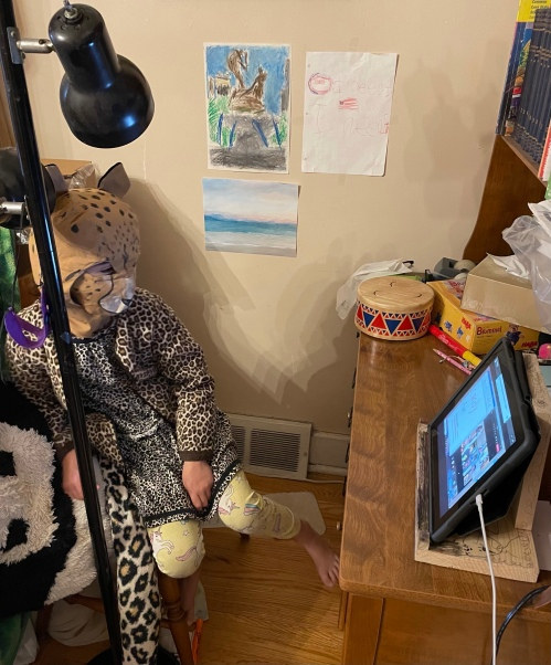 child wearing a cloth cheetah hood with attached face mask; jacket, dress, and tail in assorted cheetah/leopard prints; and yellow pajama pants with unicorns, sitting in front of a video meeting on a tablet in a homemade wooden stand much scribbled with ballpoint pen, at a desk strewn with school supplies and a small drum