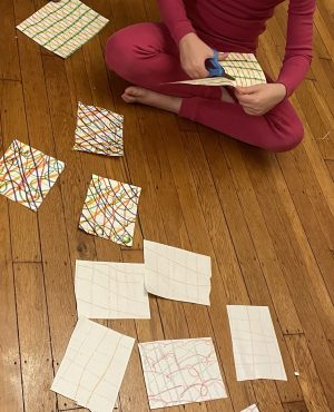 child cutting up paper on which complex plaid patterns have been drawn with markers