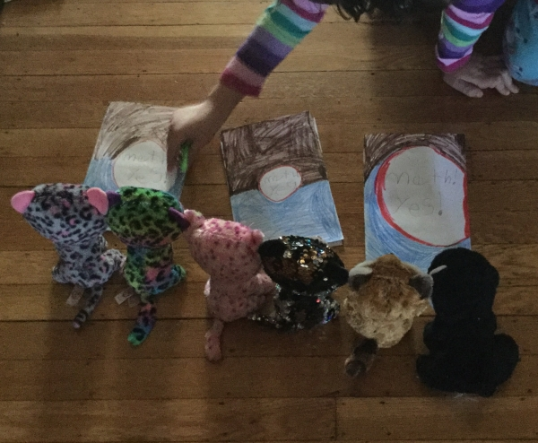 homemade math textbooks being placed in front of stuffed animals